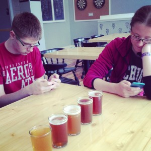 """My teens being teens [twins Kaylee and David, almost 16] on their phones while Mike and I sample beers at Brewery Ferment >> in Traverse City after Bayshore."""