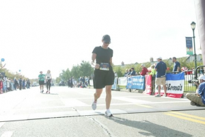 "Lorrie crossing the finish line at the first race she did after she had completed her chemotherapy--""Note the hat!"" she says. ""It was a 10K walking event and it was a goal of mine to be able to complete the event. Mission accomplished!"""