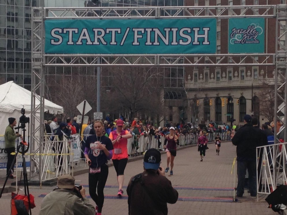Finishing the 2014 Gazelle Girl Half Marathon in Grand Rapids. (I'm the runner wearing the white hat, about to cross the finish line - thanks to Katie for capturing this moment!)