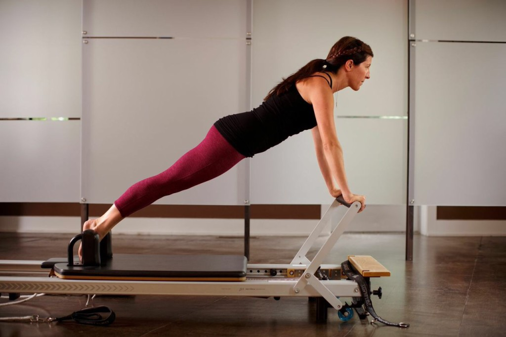 Heather, shown in plank position on the Pilates reformer.