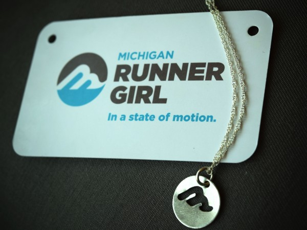 """The Michigan Runner Girl Charm Necklace: hand-cut and made in Michigan by Traverse City artist Kirsten Jones. The charm may be bought separately or with an 18"""" sterling silver chain."""